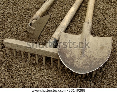 gardening tools on the ploughed ground - stock photo