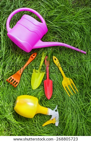 Gardening tools. Plastic watering can, mini shovel and fork on grass background - stock photo