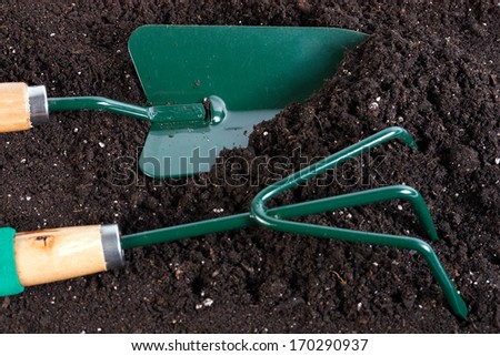 gardening tools rake and shovel on land background - stock photo