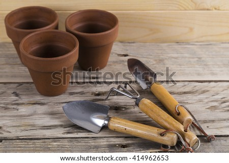 Gardening tools with three pots - stock photo