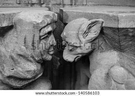 Gargoyle and monk. Church of Saint Pierre in Caen (Basse Normandie, France). Black and white. Metaphor for the Shame idea. - stock photo