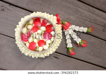 Garland Flowers made from Jasmine, Rose Petals and Crown flowers with a small silver bowl contain water and flower corolla on top isolated on wooden background (Use for Songkran Holiday in Thailand) - stock photo