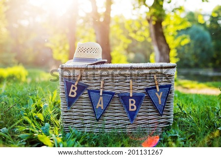 garland with the word baby on the basket on the nature - stock photo