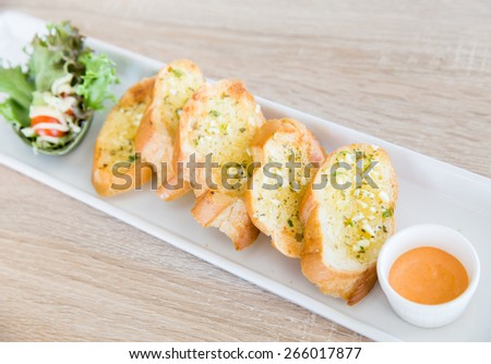 Garlic and herb bread on wooden table - stock photo