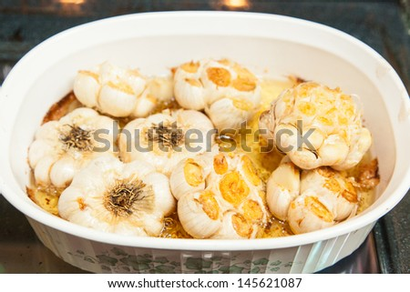 Garlic becomes sweet, mellow, and nutty when roasted. Squeeze the flesh out of the cloves and spread on bread for a great appetizer or side dish. - stock photo