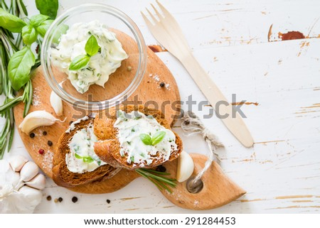 Garlic bread - baguette slices, garlic butter, herbs, wood board, white wood background, top view - stock photo