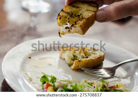 Garlic bread held by diner with plate in the background - stock photo