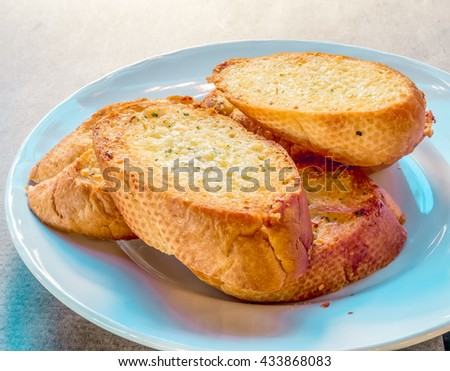 Garlic bread on white dish on table for appetizer - stock photo