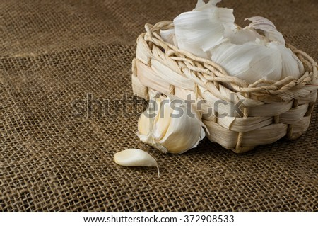 Garlic cloves in a small basket on jute tablecloth  - stock photo