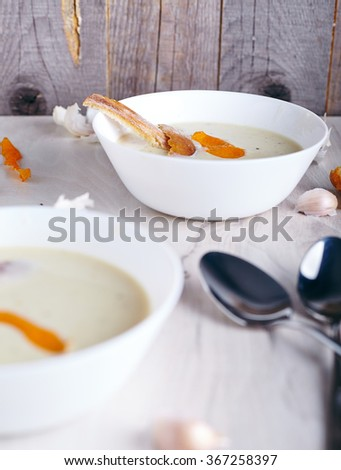 Garlic cream soup in white bowl and white wood background. Garlic cloves, spoons and ciabatta crutons near it. - stock photo