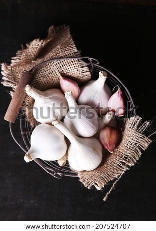 Garlic in basket on black wooden background - stock photo