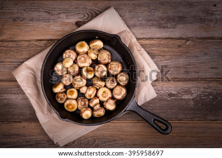 Garlic mushrooms cooked in a cast iron skillet, resting on greaseproof paper on old table. Overhead view with retro style processing. - stock photo