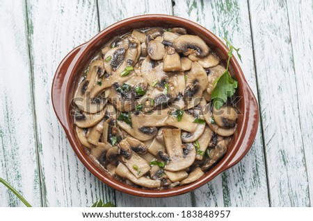 Garlic mushrooms with white wine and parsley - stock photo