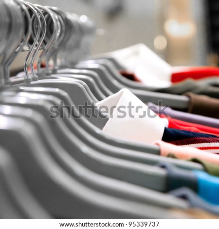 garment hanging on hangers in a store - stock photo