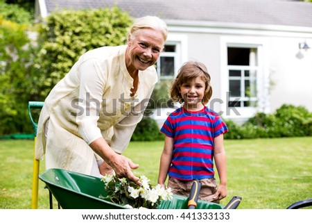 Garndmother and boy with flower pots in wheelbarrow at yard - stock photo