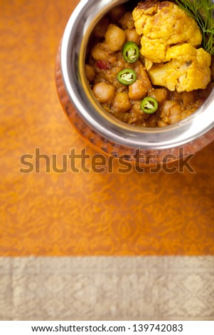 Garnished Aloo Gobi in a copper bowl. - stock photo