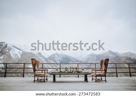 garnished and served with a table and two chairs for two vintage on a wooden terrace with views of the mountains and the snow-capped peaks - stock photo