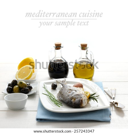 Garnished grilled sea bream with lemon, olives and oil, text space - stock photo