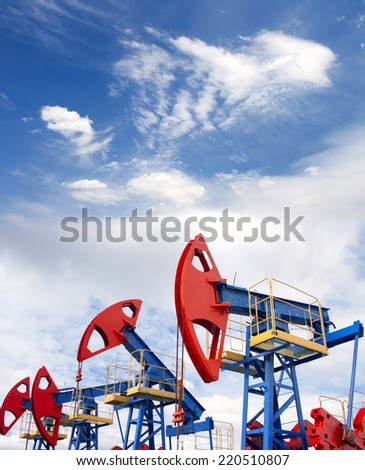 Gas and oil industry. Work of oil pump jack on a oil field. Blue sky and white clouds - stock photo