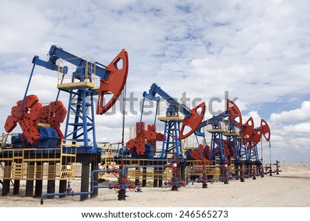 Gas and oil industry. Work of oil pump jack on a oil field. White clouds, blue sky, desert - stock photo