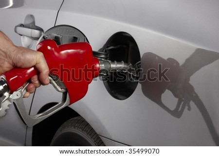 Gas attendant fills car with gasoline - stock photo