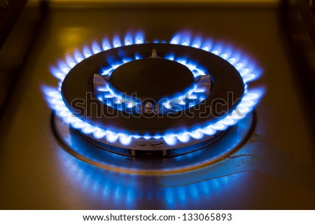 Gas burner from a stove with a blue flame - stock photo