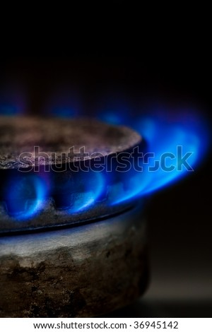 Gas burning by a dark blue flame on  kitchen - stock photo