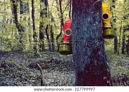 gas mask behind tree in the jungle - stock photo