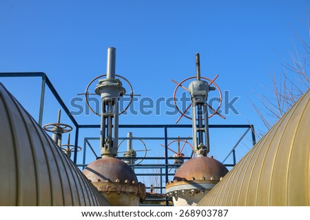 Gas pipes with valves on a background of blue sky - stock photo