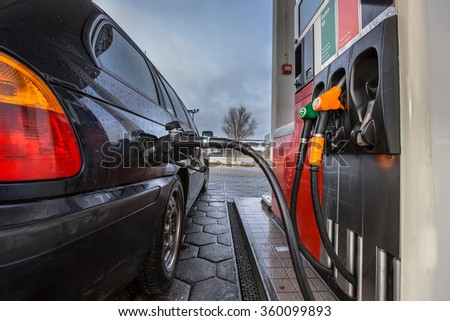 Gas pump fill at a gas station car close up on a rainy februari day with dark colors in the Netherlands - stock photo