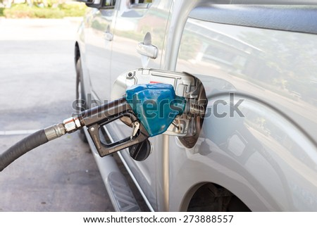 Gas pump nozzle blue in the fuel tank of a bronze car. - stock photo