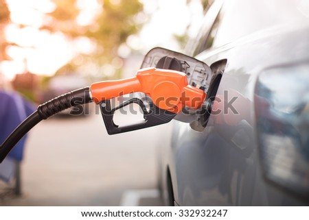 Gas pump nozzle in the fuel tank of a bronze car, refuel - stock photo