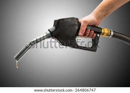 gas pump nozzle with hand and petrol drop on black background - stock photo