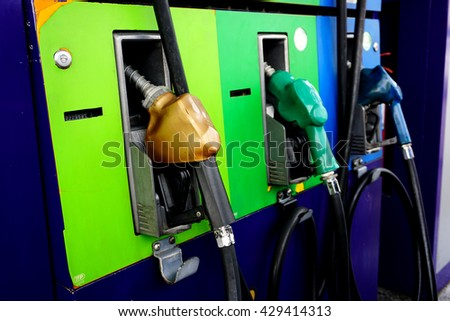 Gas pump nozzles in a service station- selective focus - stock photo