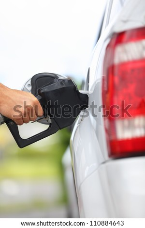 Gas station pump. Man filling gasoline fuel in car holding nozzle. Close up. - stock photo