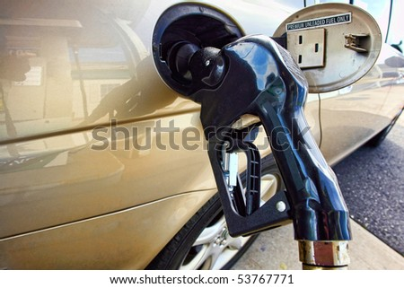 Gas station pump nozzle inserted into a car fuel tank intake to fill up the vehicle with premium unleaded gasoline - stock photo