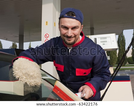 Gas Station Worker Cleaning Windshield at Service Station - stock photo