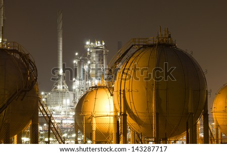 Gas storage tanks and a large oil-refinery plant - stock photo