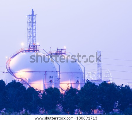 Gas storage tanks and a large oil-refinery plant in background - stock photo