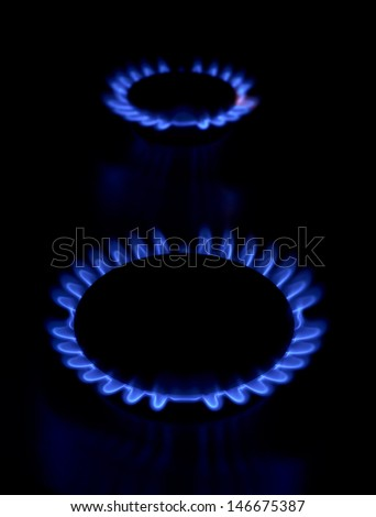 Gas stove as a blue fire lights in the dark - stock photo