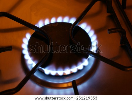 Gas stove fire in the dark kitchen - stock photo
