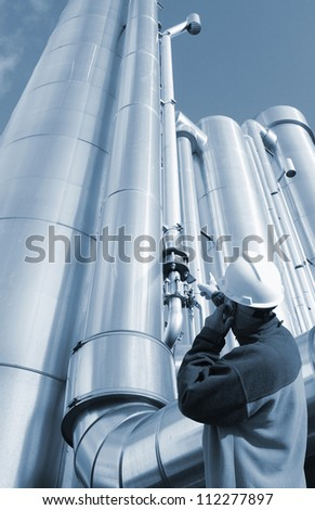 gas worker and giant gas pipelines, blue toning idea - stock photo