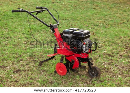 Gasoline cultivator for small agricultural works on green grass field - stock photo