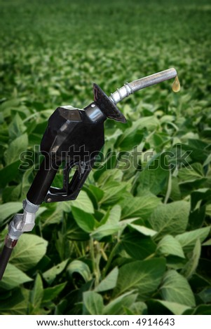 gasoline nozzle with droplet and soybean field in background - stock photo