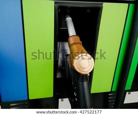 Gasoline pump nozzles at petrol station - stock photo