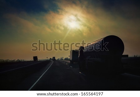 Gasoline tanker rides the highway in the evening sun rays - stock photo