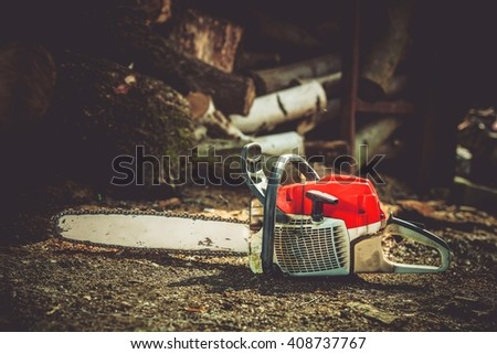 Gasoline Wood Cutter Works. Wood Cutting Gasoline Power Tool and Wood Logs in the Background. - stock photo