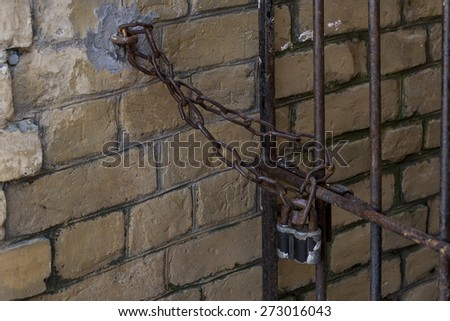 gate closed on old padlock - stock photo