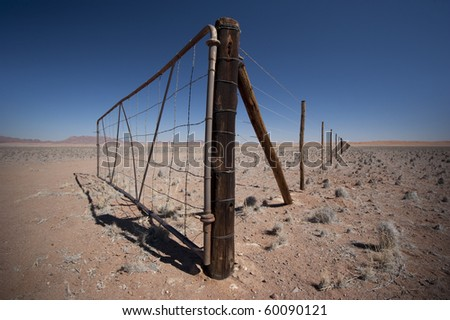 Gate somewhere in Namibia with fence disappearing in the distance. - stock photo
