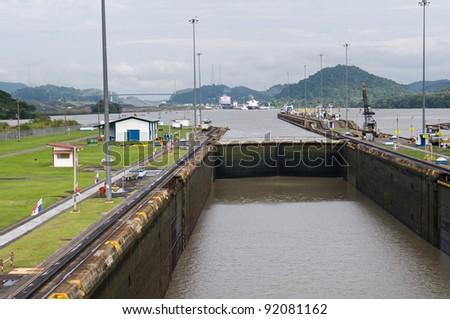 Gates and basin of Miraflores Locks Panama Canal filling to raise a ship - stock photo